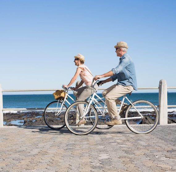 Older couple riding bikes near the ocean