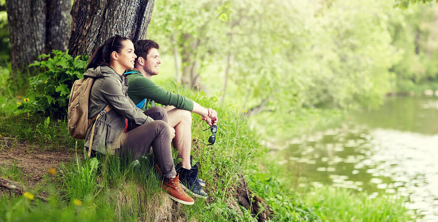 Couple sitting by the river during a hike