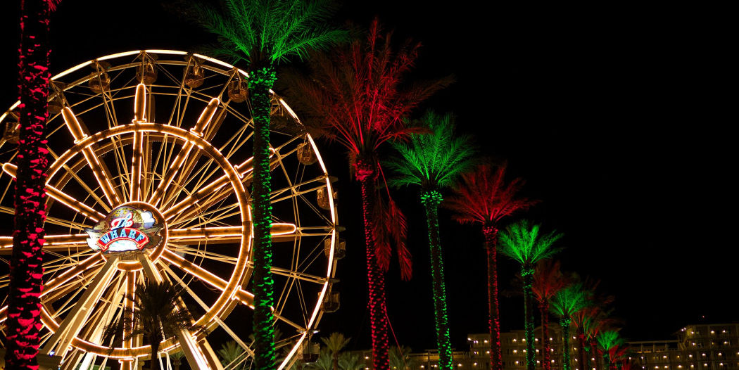 A Ferris wheel with lit palm trees