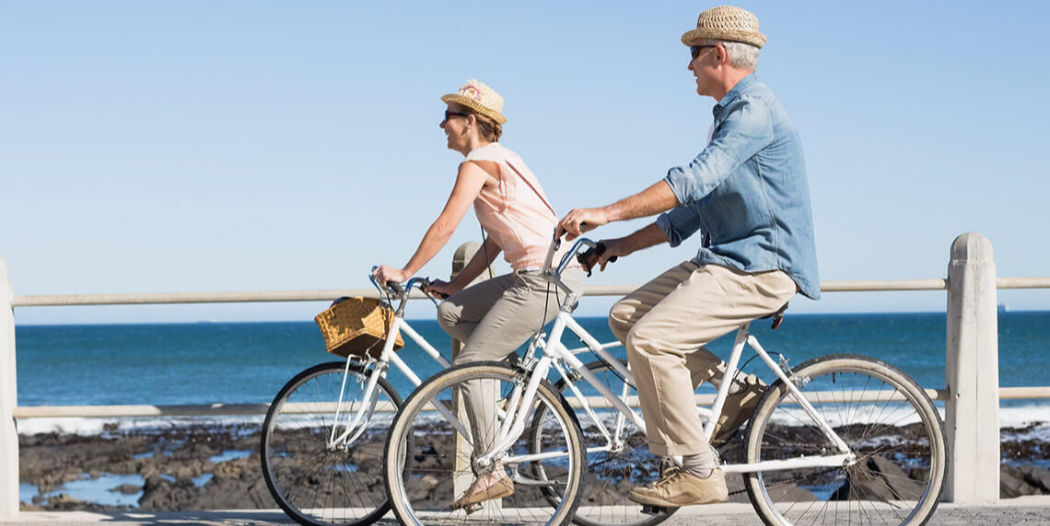 Older couple riding bikes near the ocean