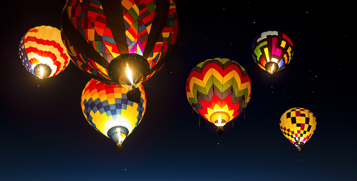 A group of hot air balloons at dusk