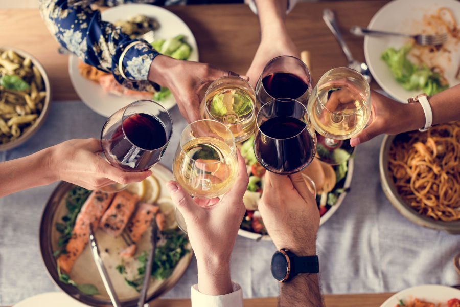 Group cheering wine over plates of food in Gulf Shores