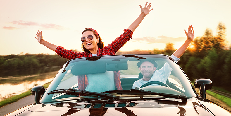 Man and woman smiling in a car